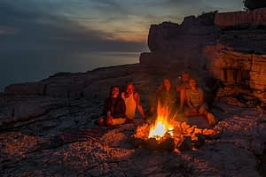 Group sitting beside a camp fire